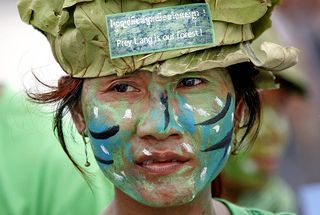 """Cambodia's """"Avatars"""" - A local activist dresses in traditional Kuy garb with her face painted like the famous movie characters, calling on the government to take action to protect the Prey Lang Forest."""